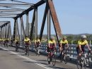 men-riding-bikes-across-bridge