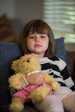 Child looking sad with a teddy bear