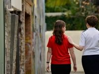A Salvation Army worker walks through a rough back street with a young woman