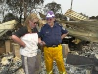 A man and a woman look at the aftermath of a fire.
