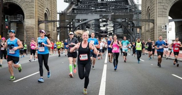 girl running and smiling on Sydney Harbour Bridge