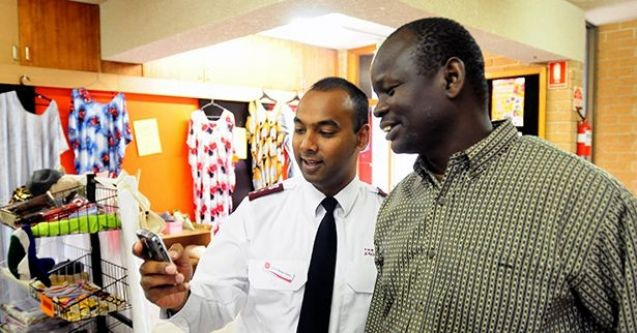 Salvation Army officer looking at mobile phone with migrant