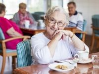 Senior smiling over a cup of tea and a biscuit