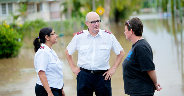 Officers talking to a woman affected by the Queensland flood