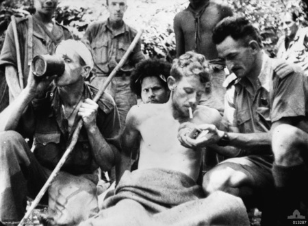 A wounded Australian soldier has his cigarette lit by Salvation Army Chaplain Albert Moore, padre to the 2/14th battalion. The soldier on the stretcher is VX51106 Lieutenant Valentine G. Gardner, D Company, 2/14th Battalion. An unidentified soldier on the left having a drink has a bandaged head and is carrying a staff. A Papuan stretcher bearer (popularly known as a Fuzzy Wuzzy Angel) is behind the stretcher. (Frame enlargement from AWM films, F01212 or F01582 taken by Damien Parer).