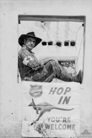 Captain Allan Daly, Salvation Army Red Shield Defence Service Representative, in a slouch hat, sits in the window frame at the Salvation Army point